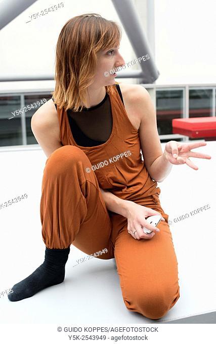 Arnhem, Netherlands. Young brunette ballet dancer taking a break from training and rehearsal just outside her ballet studio