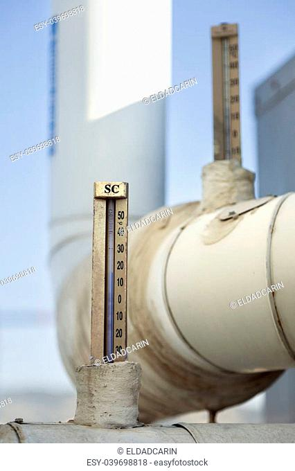 Couple of Celsius thermometers, connected to water pipes which are a part of HVAC commercial air-conditioning system. Water temperature is approximately 15°c