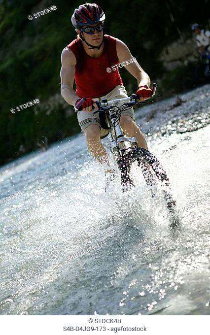 Young man on a mountainbike in a rivulet, selective focus