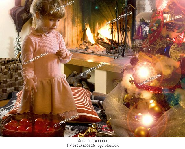 little girl holding a basket with red christmas balls