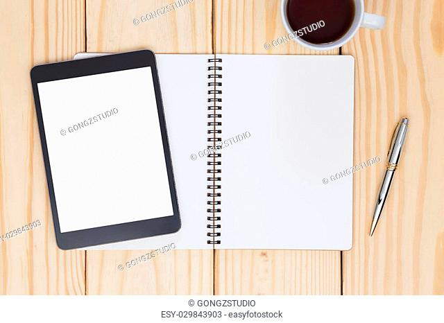 Blank notebook and white screen tablet on wood table