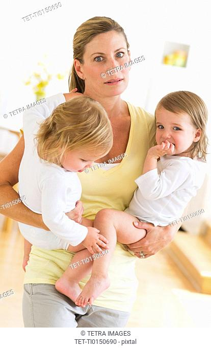 Mother holding daughters 2-3 and making facial expression