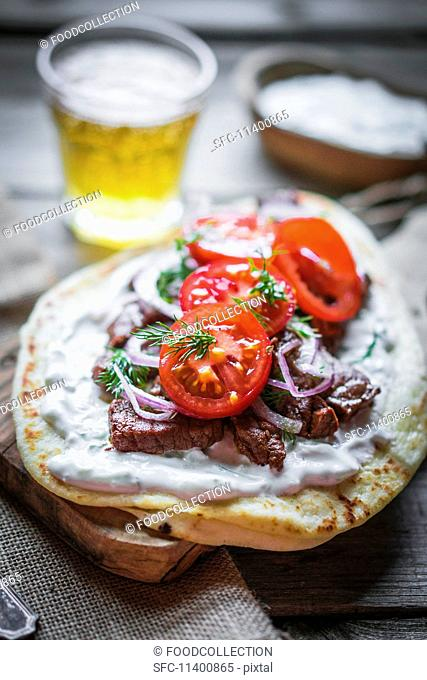 Pita bread topped with beef, cream cheese, tomatoes and onions