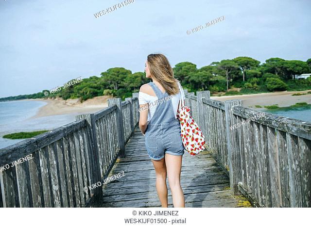 Back view of woman walking to beach on boardwalk