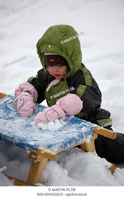 little girl playing with snow on toboggan