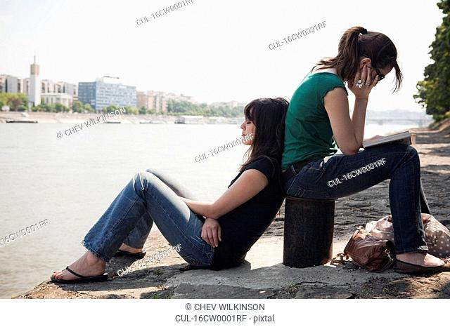 Two women sitting by river