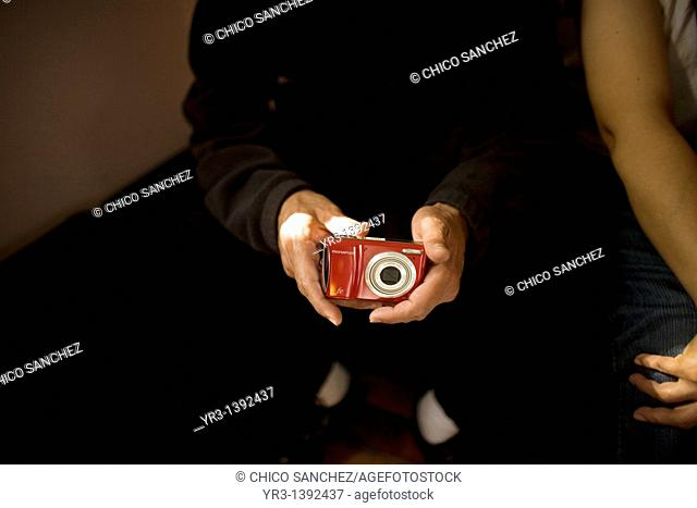 A blind male student touches a camera