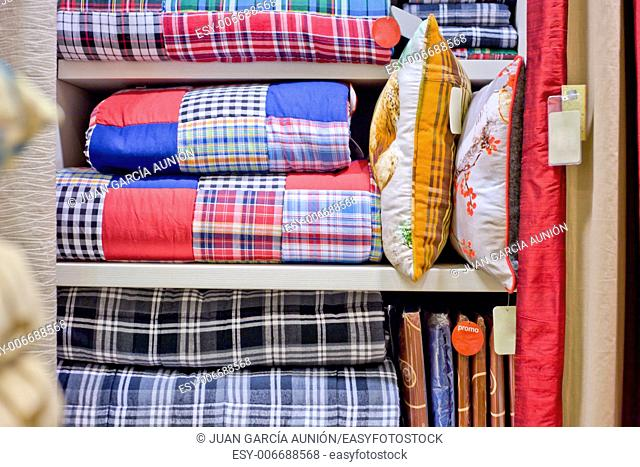Bright pillows, plaids, blankets and other bedroom wear on shelves