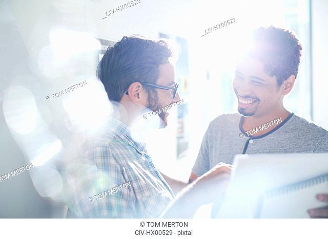 Smiling creative businessmen using digital tablet in sunny office