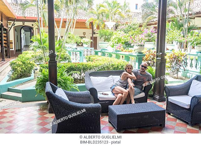 Smiling Caucasian couple on sofa in hotel courtyard