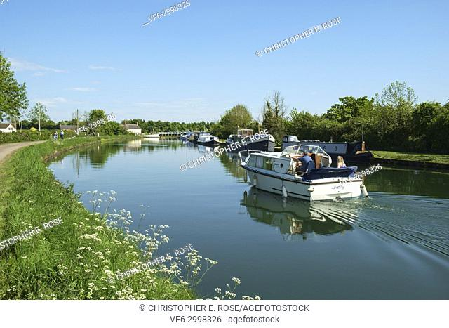 A small boat cruises towards the swing bridge at Purton Gloucester & Sharpness Canal at Purton in summer sunshine, Gloucestershire, UK