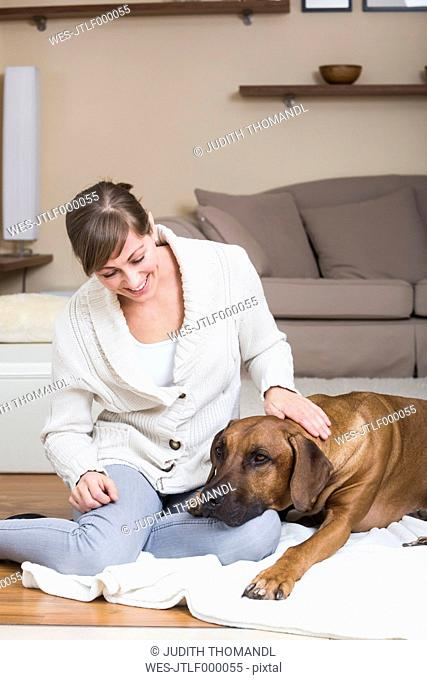 Woman caressing her Rhodesian Ridgeback dog