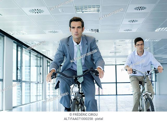 Businessmen riding bicycles indoors