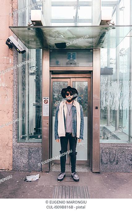 Portrait of young man standing in doorway