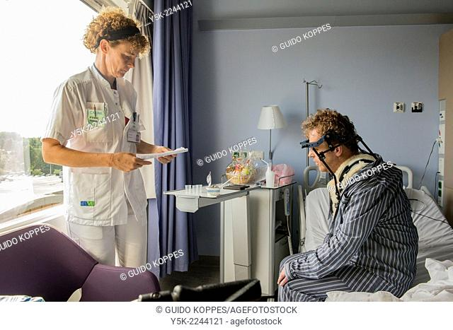 Tilburg, Netherlands. Physio therapist instructing a post operative patient with fractured cervical on how to walk again, after a head brace is mounted