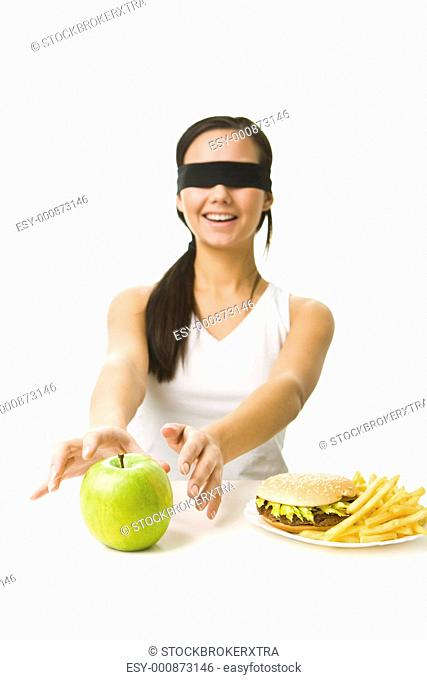 Portrait of young girl with her eyes folded deciding what to eat: an apple or fast food