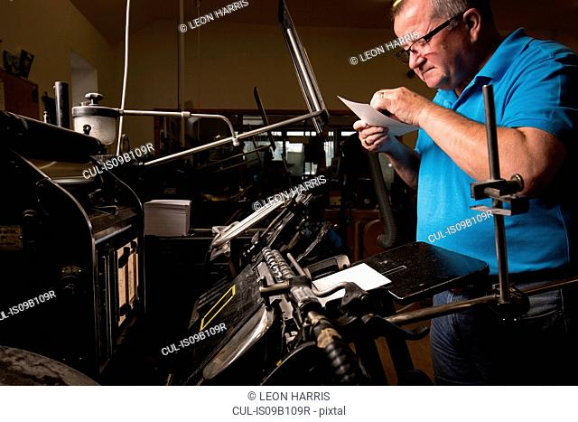 Mature male printer inspecting paper for printing machinery in printing press workshop