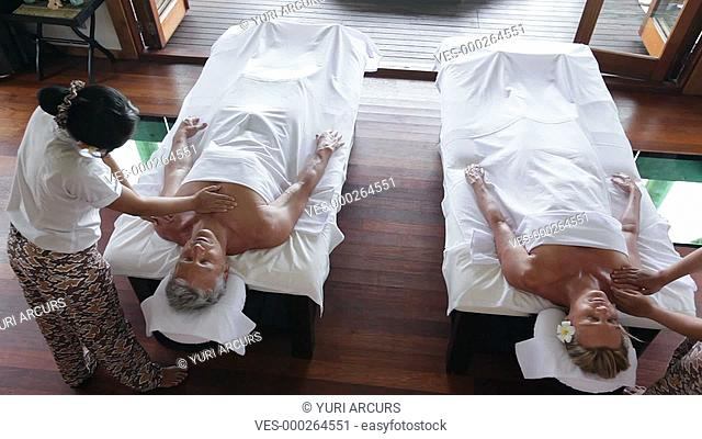 Topview of a couple receiving luxurious massages, with a slow pan to the left focussing on the man
