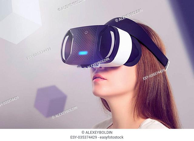 Woman in VR headset looking up at the objects in virtual reality. VR is a computer technology that simulates a physical presence and allows the user to interact...