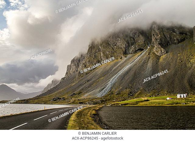The ring road and mountains in the clouds next to the shore of the Norwegian Sea in the hamarsfjord nearby Dj£pivogur in Iceland