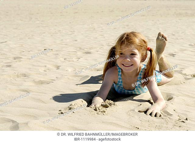 Girl lying and playing at the beach, seaside of the Adria, Bibione, Venetia, Venice, Italy, Europe