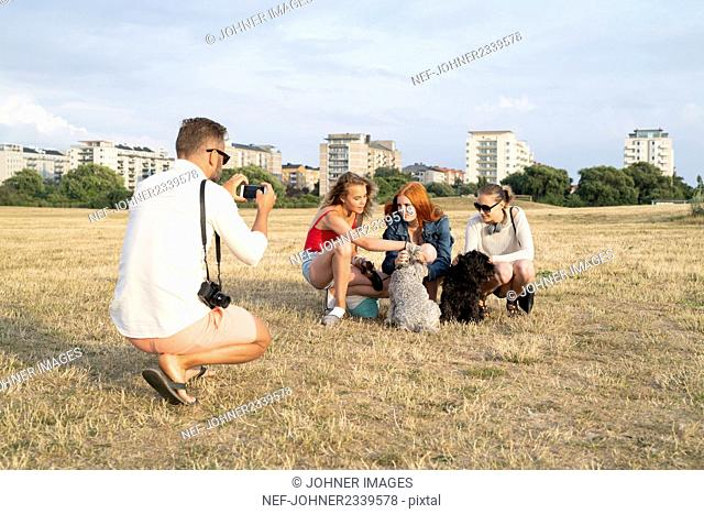 Father photographing his family playing with dogs