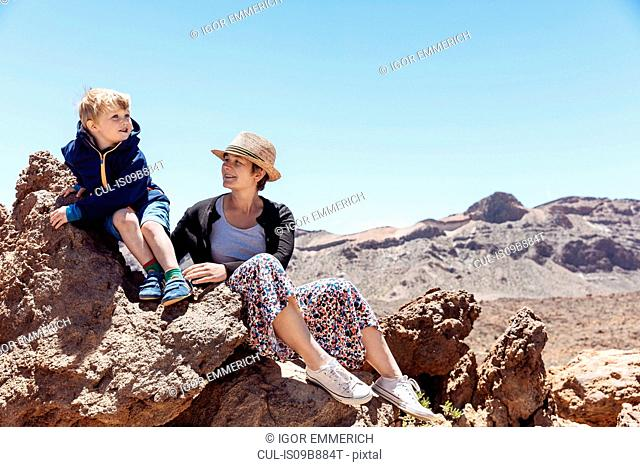 Boy and mother sitting on rocks at Mount Teide, Tenerife, Canary Islands