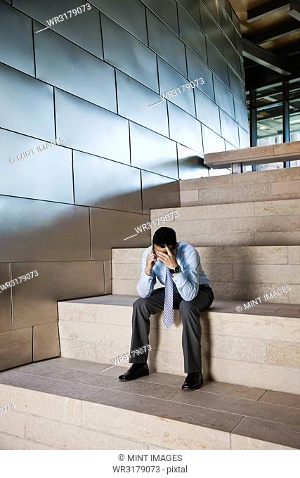 Businessman in a stressful situation while on a cell phone in the lobby of a large office building