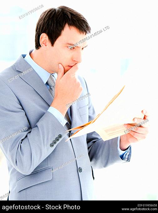 Portrait of a thinking businessman reading a newspaper