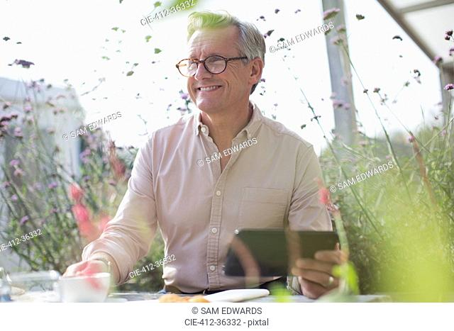 Smiling senior man using digital tablet on sunny patio
