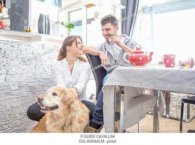 Young couple having breakfast, with dog