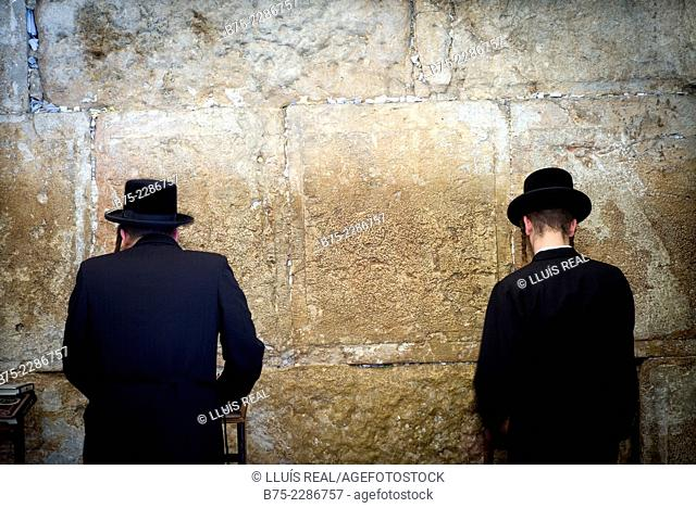 Two unrecognizable jewish man seen from behind, praying in the synagogue in Wailing Wall Western Wall Plaza, Jewish Quarter, Jerusalem, Israel