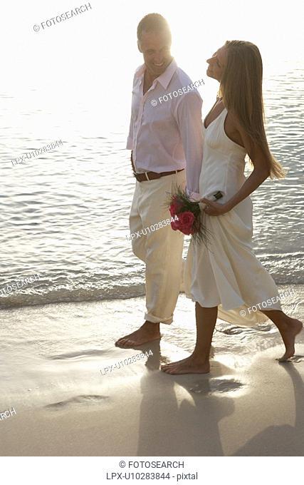 Newlyweds walking on sandy beach, St John, US Virgin Islands, USA