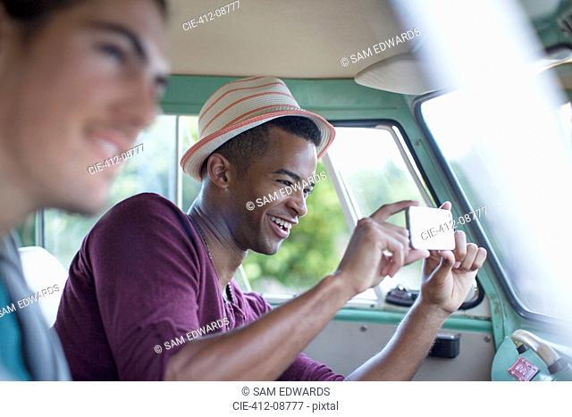 Man using camera phone in camper van
