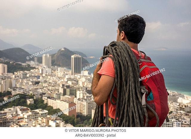 Male adult climber on rocky edge with a view to mountains and the city, Agulinha de Copacabana in Rio de Janeiro, Brazil