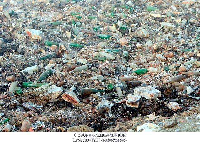 Large garbage dump waste with broken bottles