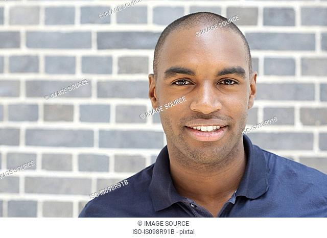 Portrait of young man in front of wall