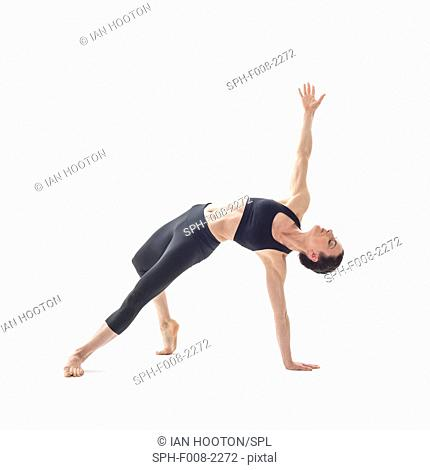 MODEL RELEASED. Woman practicing yoga. This is a variation of the side plank pose