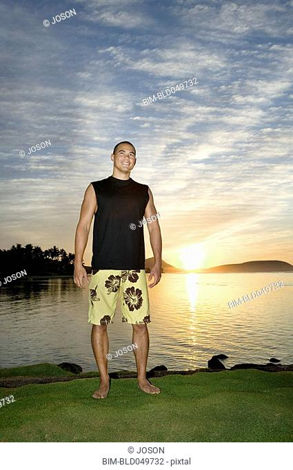 Asian man next to water at sunset