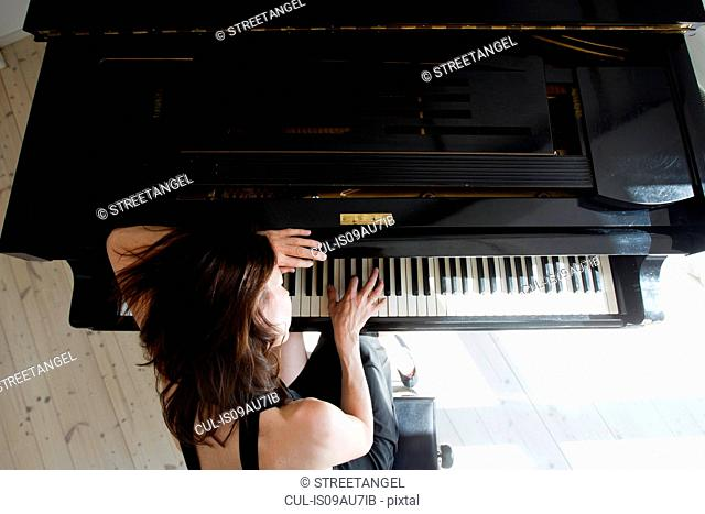 Overhead view of mature woman leaning on piano playing