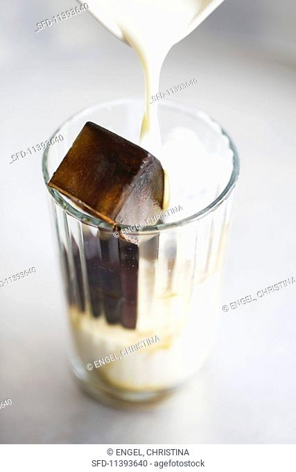 A glass with an espresso ice cube and milk