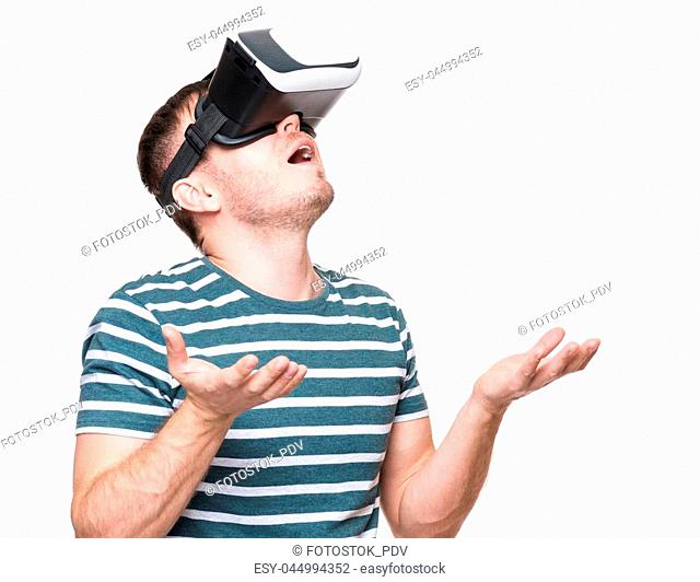 Amazed handsome man wearing virtual reality goggles watching movies or playing video games gesticulating hands. Surprised male looking in VR glasses