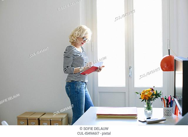 Mature woman at home writing in notebook