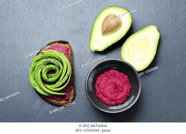 Rye breakfast sandwich with beet hummus and avocado