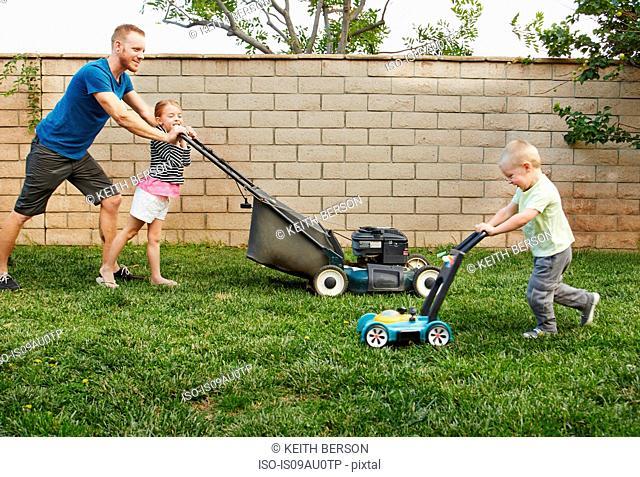 Family mowing lawn in backyard