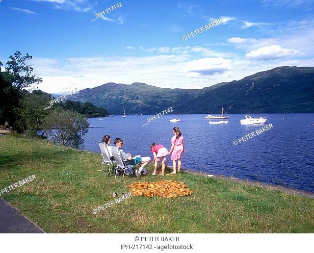Family relaxing beside Loch Lomond