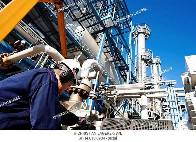 MODEL RELEASED. Worker checking pipework on an oil and gas refinery