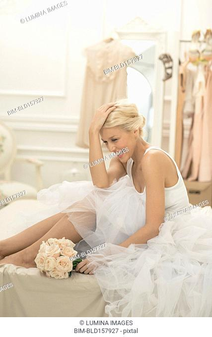 Laughing bride sitting with bouquet on bed