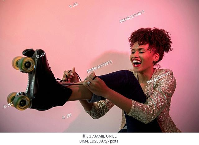 Glamorous Black woman tying roller skate