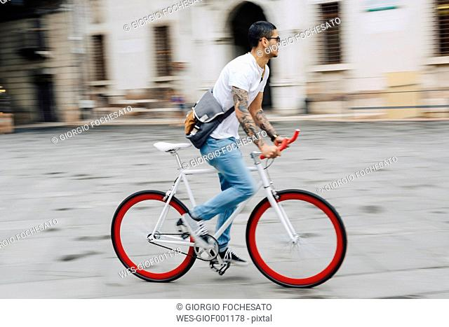 Young man riding bicycle in the city